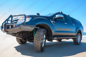Low profile view of the PX Ford Ranger (Dual Cab) on the beach fitted with a set of nitro gas struts, coils and rock sliders
