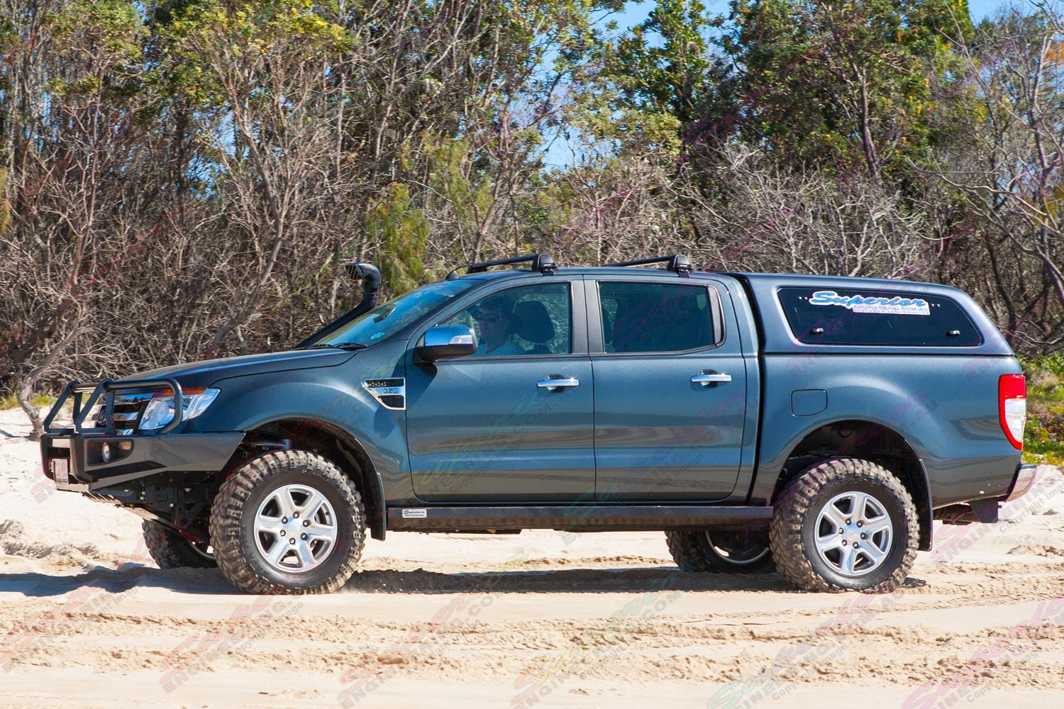 Left side view of a black PX Ford Ranger (Dual Cab) on some soft sand fitted with a 2 inch Superior Engineering nitro gas lift kit