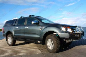 Front right view of a Dark Grey Ford Ranger dual cab fitted with superior upper control arms, rock sliders, diff guard, bash plate, recovery point and transfer case guard