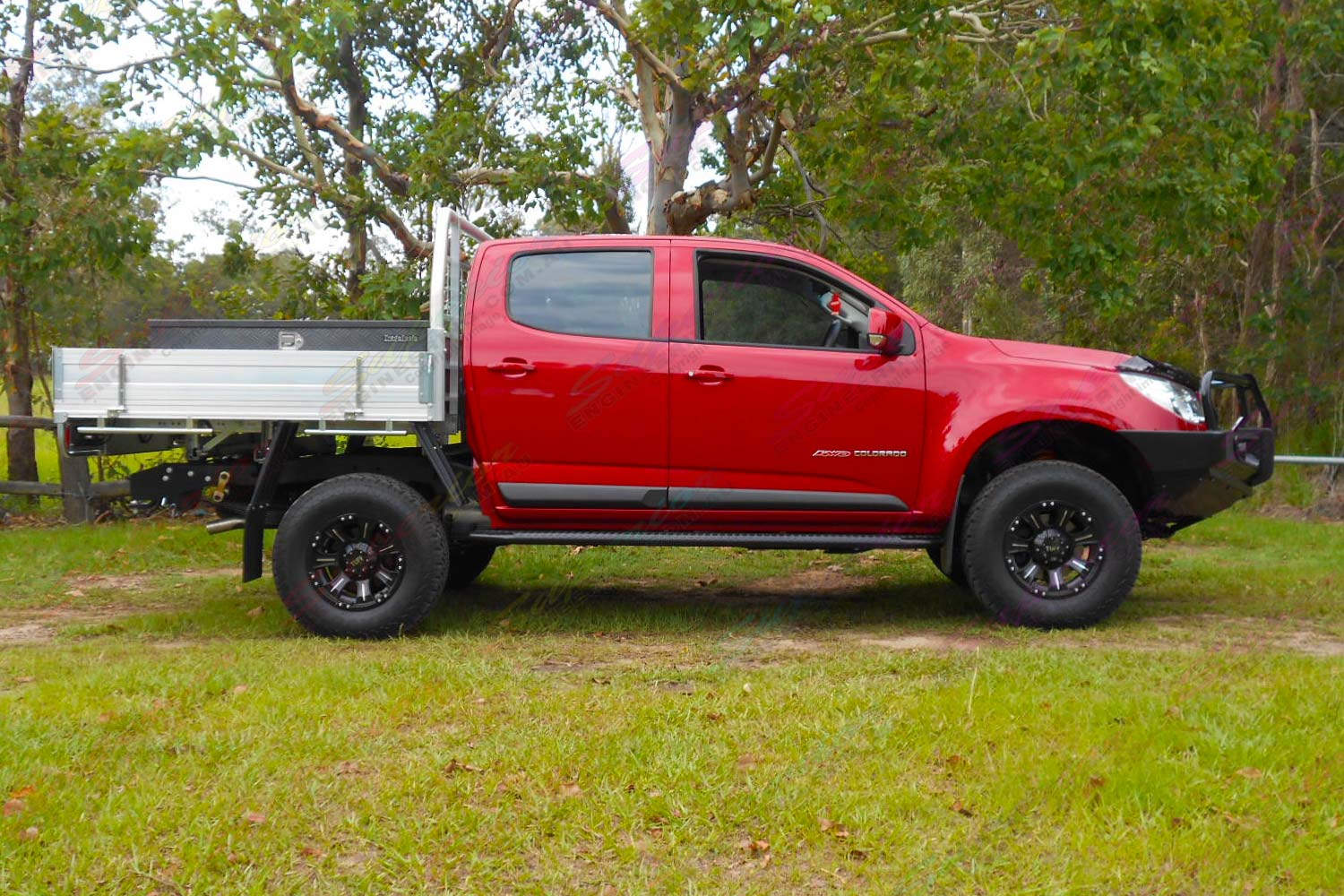 """Right side profile of a Red Holden Colorado RG Dual Cab fitted with a Superior 2"""" lift kit, Ironman Bullbar and sidesteps"""