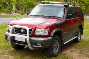 Front left angle view of a red Holden Jackaroo wagon fitted with a 40mm Ironman 4x4 Performance lift kit and TJM Air Snorkel