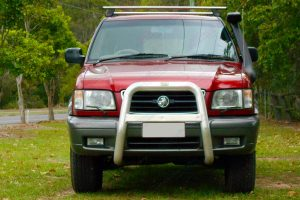 Front on view of a red Holden Jackaroo wagon fitted with a 40mm Ironman 4x4 Performance lift kit and TJM Air Snorkel