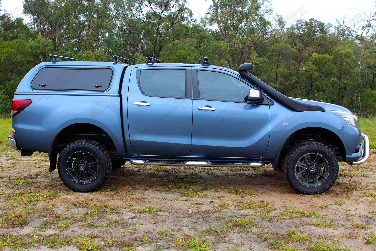 "Right side profile view of a blue Mazda BT-50 dual cab fitted with a Superior 2"" inch lift kit"