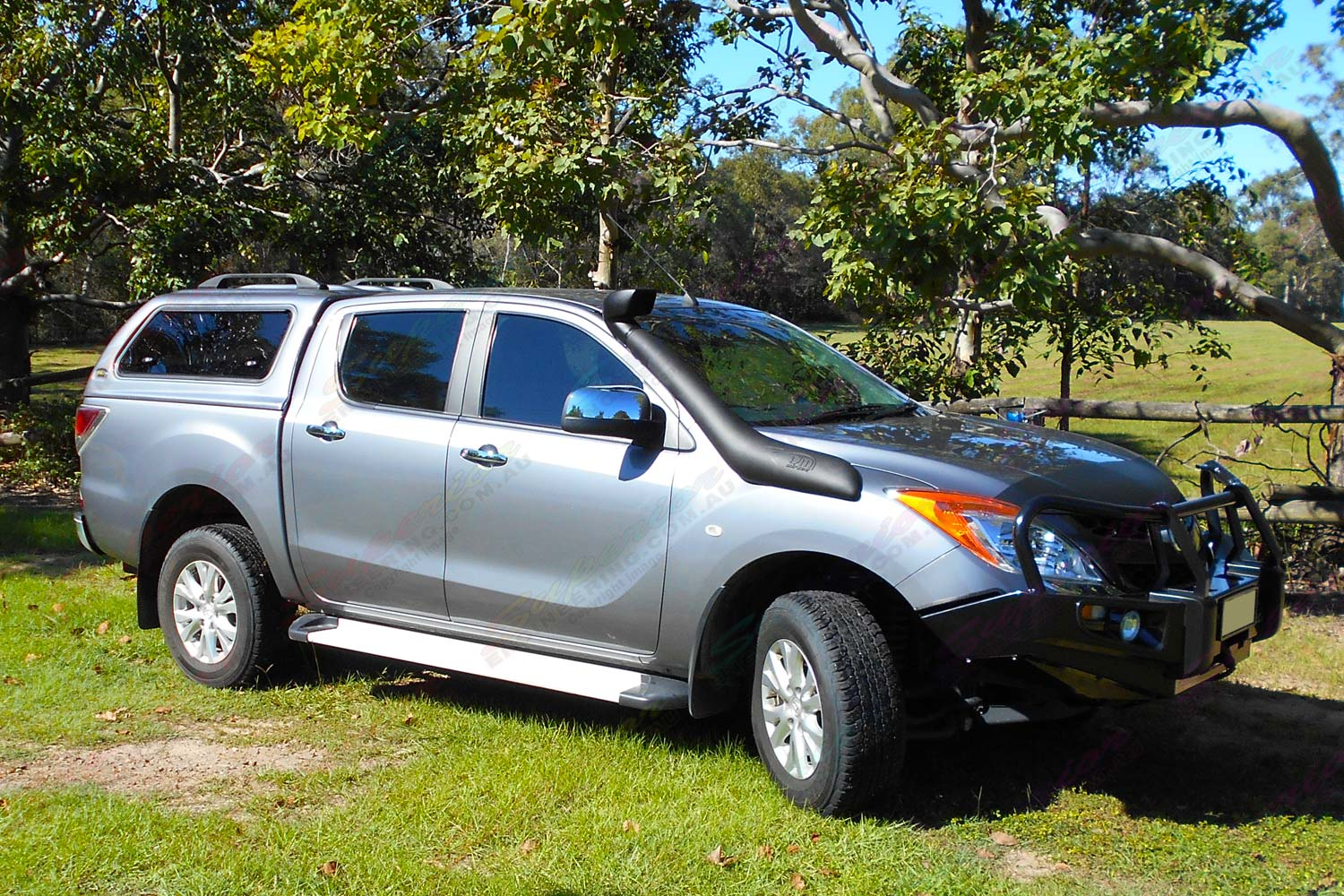 Right side view of a grey Mazda BT-50 dual cab fitted with a Black Ironman Deluxe Commercial Bullbar, Ute canopy and TJM airtec snorkel