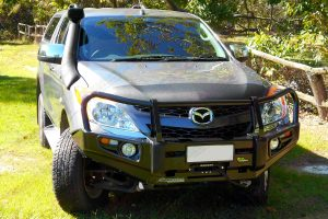 Front on view of a grey Mazda BT-50 dual cab fitted with a Black Ironman Deluxe Commercial Bullbar, Ute canopy and TJM airtec snorkel