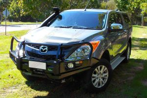 Front left side angle view of a grey Mazda BT-50 dual cab fitted with a Black Ironman Deluxe Commercial Bullbar, Ute canopy and TJM airtec snorkel