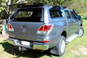 Rear end view of a grey Mazda BT-50 dual cab fitted with a Ironman Ute canopy with all the windows open