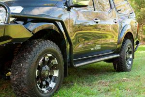 Closeup view of an Ironman 4x4 side step and rail fitted to a Black NP300 Nissan Navara dual cab