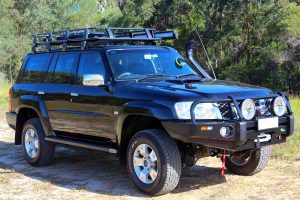"""Front right angle view of a GU Nissan Patrol Wagon fitted with a 2"""" lift kit, bullbar, winch, rock sliders, spot lights, exhaust system and more"""