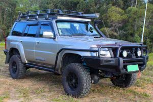 """Front right side view of a Gold GU Nissan Patrol Wagon fitted with a 3"""" Inch Superior Remote Reservoir Superflex Lift Kit"""
