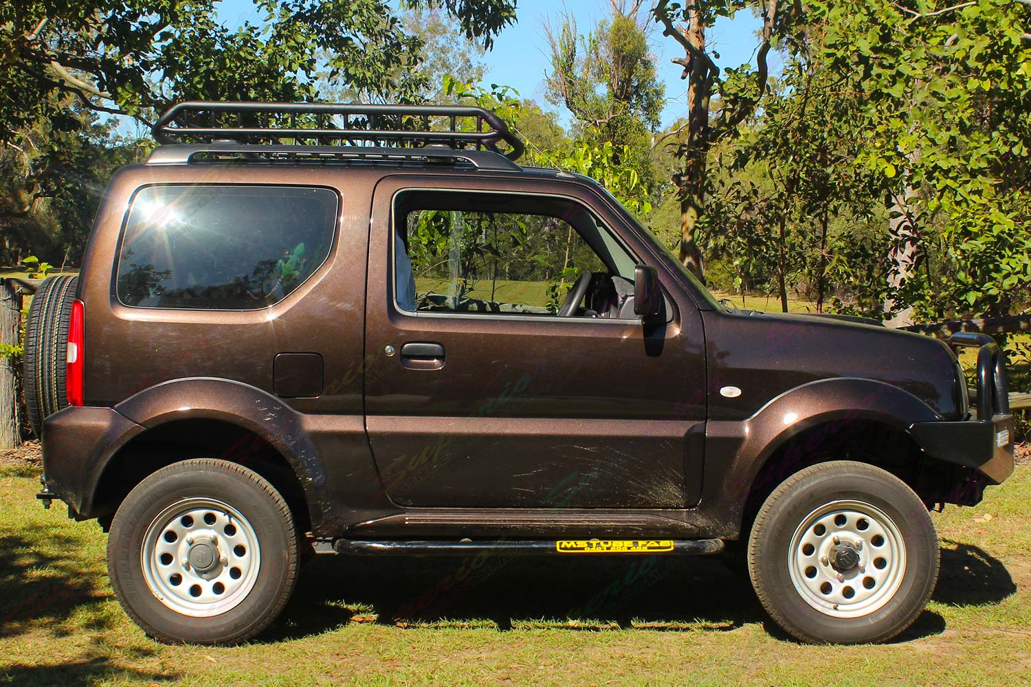 Right side view of a brown Suzuki Jimny Sierra Wagon fitted with a heavy duty 60mm Tough Dog lift kit