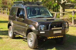 Front right view of a brown Suzuki Jimny Sierra Wagon fitted with a massive 60mm Tough Dog 4x4 lift kit