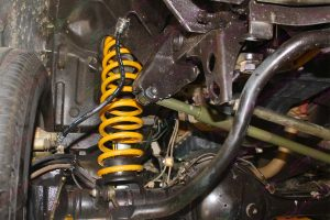 Closeup view of the Tough Dog Panhard Rod mount, extended brack hose and coil spring fitted to the Suzuki Jimny Sierra