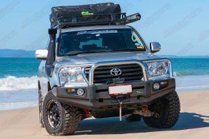 Front view of a 200 Series Toyota Landcruiser on the beach fitted out with a Profender 2 Inch Lift Kit and Ironman 4x4 accessories