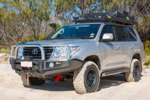 Front left side on view of a 200 Series Toyota Landcruiser on the beach fitted out an Ironman 4x4 bullbar, roof top tent, annex, snorkel and winch