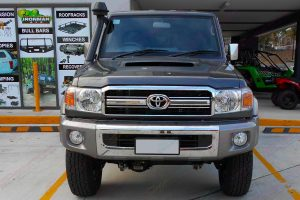 Full front view of a dark grey 76 Series Toyota Landcruiser wagon fitted with a Superior Remote Reservoir Superflex 4 Inch Lift Kit