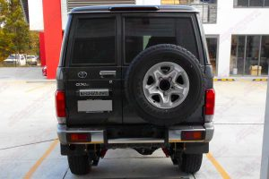 Rear end view of a dark grey 76 Series Toyota Landcruiser wagon fitted with a Superior Remote Reservoir Superflex 4 Inch Lift Kit