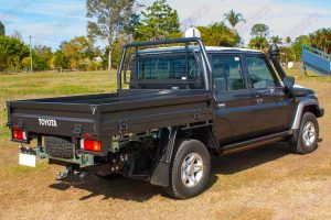 Rear right side view of a Brand NEW 79 Series Dual Cab Toyota Landcruiser fitted with a set of heavy duty Superior Engineering Stealth Rock Sliders