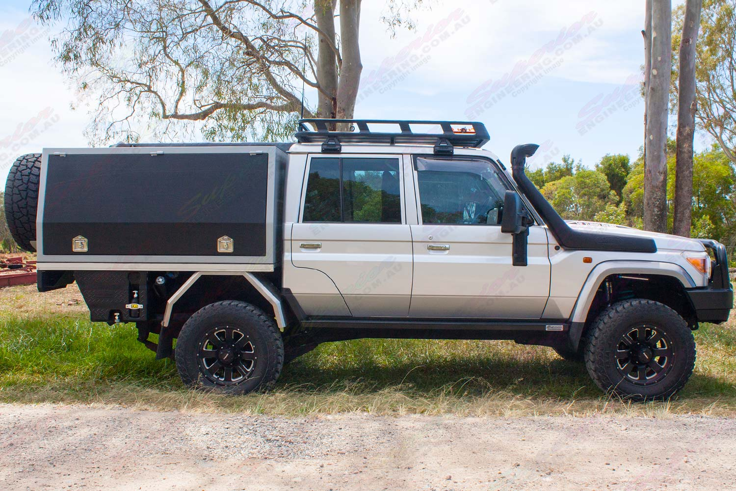 Right side view of a silver 79 Series Toyota Landcruiser (Dual Cab) fitted with a set of heavy duty Superior Engineering Stealth Rock Sliders
