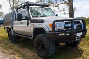 Front right view of a silver 79 Series Toyota Landcruiser (Dual Cab) fitted with a set of heavy duty Superior Engineering Stealth Rock Sliders