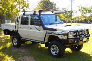 Front right side view of a white 79 Series Toyota Landcruiser (dual cab) fitted with a heavy duty Superior 4 Inch Lift Kit