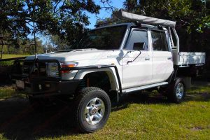 Front left side view of a white 79 Series Toyota Landcruiser (dual cab) fitted with a heavy duty Superior 4 Inch Lift Kit featuring Tough Dog shocks