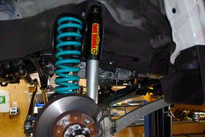 Closeup view of a 45mm adjustable Tough Dog shock and coil spring fitted to the front of a 79 Series Toyota Landcruiser