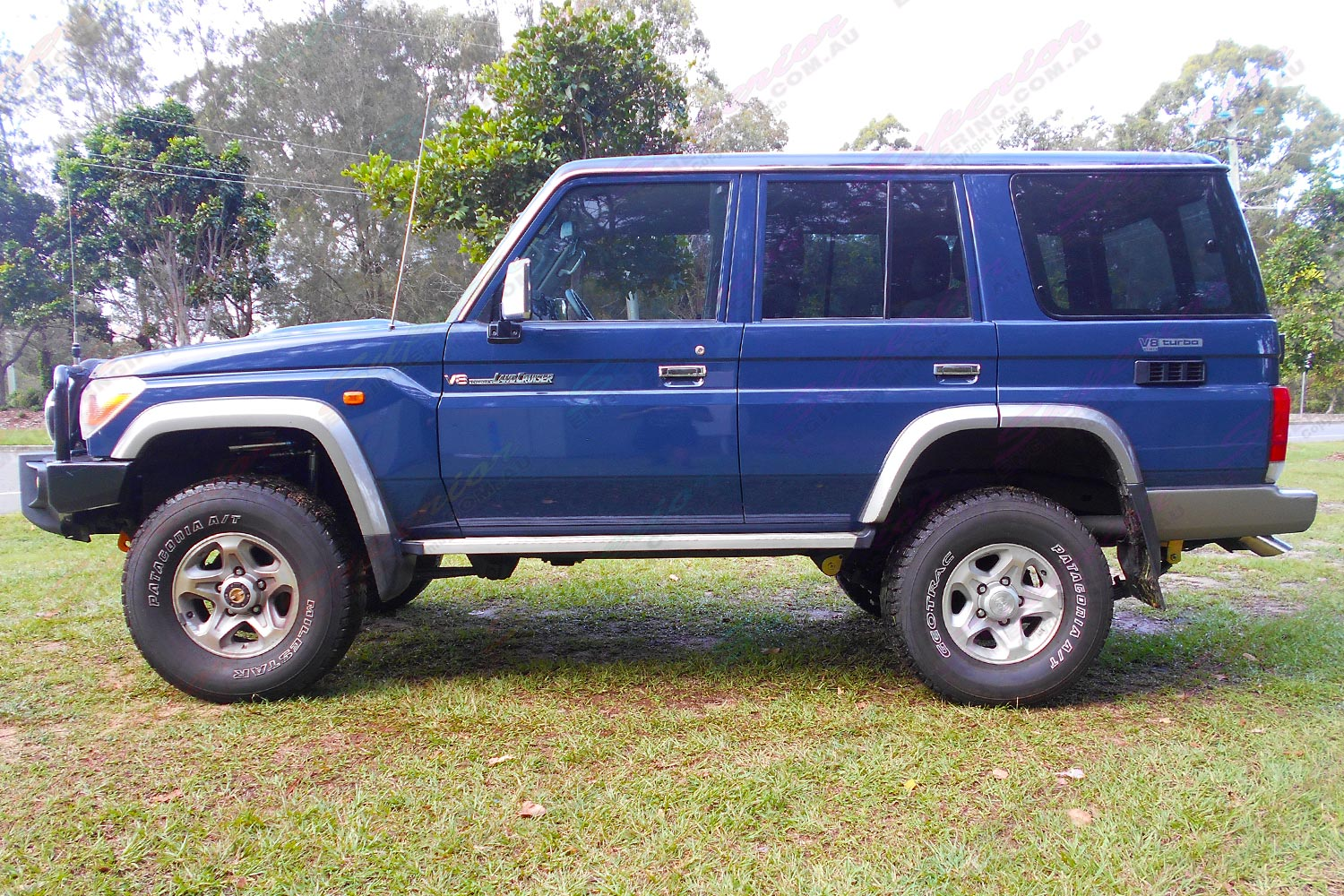 Left side view of a blue 76 Series Toyota Landcruiser wagon fitted with a Superior Remote Reservoir 2 Inch Lift Kit