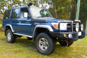 Front right view of a blue 76 Series Toyota Landcruiser wagon fitted with a Superior Remote Reservoir 2 Inch Lift Kit