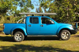 Right side view of a blue D40 Nissan Navara dual cab fitted with a 40mm Tough Dog lift kit, Ironman 4x4 bullbar & underbody protection