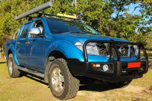 Front right angle view of a blue D40 Nissan Navara dual cab fitted with a 40mm Tough Dog lift kit, Ironman 4x4 bullbar & underbody protection