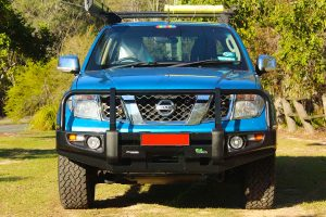 Full front view of a blue D40 Nissan Navara dual cab fitted with a 40mm Tough Dog lift kit, Ironman 4x4 bullbar & underbody protection