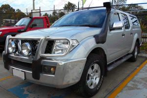 Front left side view of a silver D40 Nissan Navara dual cab fitted with a Ironman 4x4 Airforce Snorkel