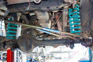 Closeup view of some Tough Dog shocks, Dobinsons coil springs and Superior Draglink and Panhard Rod fitted to the front of a GQ Nissan Patrol wagon