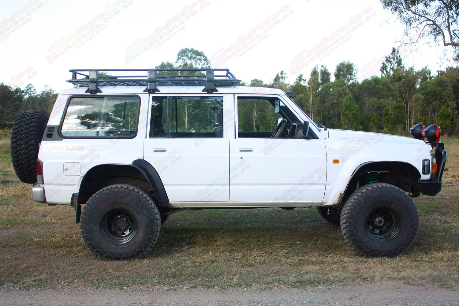 Right side view of a white GQ Nissan Patrol wagon after being fitted with a Superior Remote Reservoir Superflex 5 Inch Lift Kit