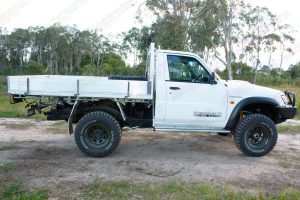 Right side view of a white GU Nissan Patrol single cab ute after being fitted with a 4 inch Superior Drop Box lift kit