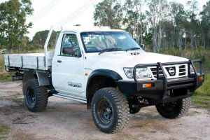 Front right view of a white GU Nissan Patrol single cab ute after being fitted with a 4 inch Superior Drop Box lift kit