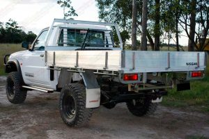 Left rear end view of a white GU Nissan Patrol single cab ute after being fitted with a 4 inch Superior Drop Box lift kit