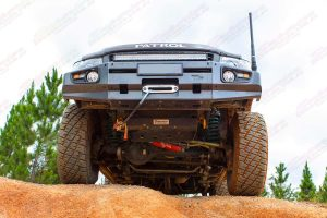 Front underside view of a MR Y61's Nissan Patrol sitting on top of a dirt hill showing off the bullbar, bash guard, panhard rod, draglink and swaybars