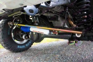 Closeup under vehicle view of the heavy duty Superior draglink, panhard rod, coil springs and AmadaXtreme steering damper fitted to the front of the GU Nissan Patrol wagon