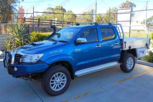 Left side view of a blue dual cab Toyota Hilux fitted with a 2 inch Bilstein lift kit, roof rack, snorkel, tool boxes, uhf radio & antenna