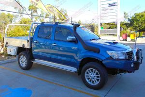 Right side view of a blue dual cab Toyota Hilux fitted with a 2 inch Bilstein lift kit, roof rack, snorkel, tool boxes, uhf radio & antenna