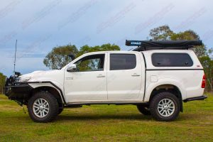 Left side view of a white dual cab Toyota Hilux fitted with a 2 inch Bilstein Suspension kit, Superior upper control arms and swaybar relocation plate