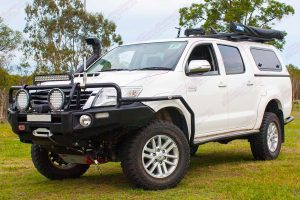 Front left view of a white dual cab Toyota Hilux fitted with a 2 inch Bilstein Suspension kit, Superior upper control arms and swaybar relocation plate