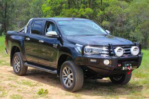 Front right view of a black Toyota Hilux Revo (Dual Cab) fitted with a premium Bilstein 2 inch lift kit