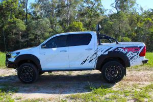 Left side view of a white Toyota Hilux Revo (dual cab) fitted with Australian made Lightforce HTX Hybrid HID LEDs and Ironman 4x4 side steps, sportsbar, flood lights and rear protection bar - by Superior Engineering