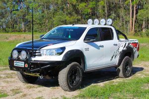 Front left view of a Toyota Hilux Revo (dual cab) fitted with premium Lightforce HTX Hybrid HID LEDs and Ironman 4x4 side steps, sportsbar, flood lights and GME Antenna - by Superior Engineering