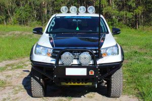 Full front view of a Toyota Hilux Revo fitted with premium Lightforce HID LEDs, Ironman 4x4 flood lights and GME Antenna