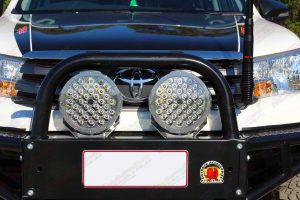 Closeup view of a pair of Ironman 4x4 flood lights fitted to the front bullbar of a Toyota Hilux Revo