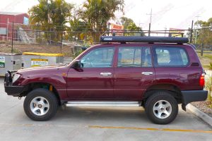 Left side view of a maroon 100 Series Toyota Landcruiser after being fitted with a heavy duty 2 inch Dobinsons 4x4 lift kit